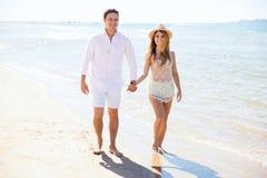 步行沿着向下海滩的逗人喜爱的夫妇 库存照片