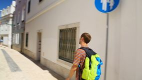 步行沿着向下狭窄的街道的男性背包徒步旅行者在镇在明亮的晴天,假日 股票录像