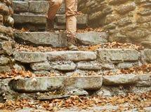 步行沿着向下石楼梯的无法认出的妇女 免版税库存照片