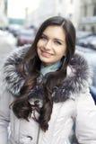 步行沿着向下积雪的街道的少妇 免版税图库摄影