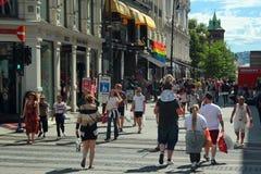 步行沿着向下繁忙的卡尔约翰门街道的人们在奥斯陆,挪威 免版税库存照片
