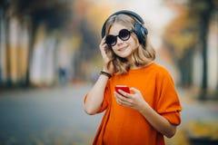 步行沿着向下老城市街道和听的音乐在耳机,都市样式,时髦的行家青少年的举行的逗人喜爱的少女 库存照片