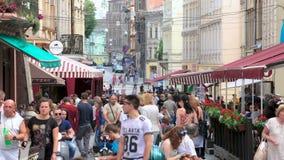 步行沿着向下老欧洲城市、旅游业和休息狭窄的街道的许多人民  股票录像