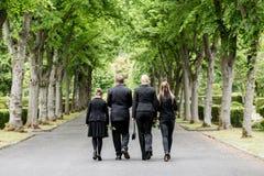 步行沿着向下胡同的家庭在坟园 库存图片