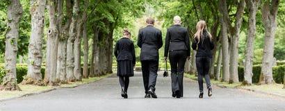 步行沿着向下胡同的家庭在坟园 免版税库存照片
