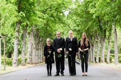 步行沿着向下胡同的家庭在坟园 库存照片