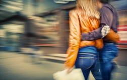 步行沿着向下街道拥抱的男人和妇女 图库摄影