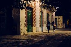 步行沿着向下街道的两个女孩在晚上 库存照片