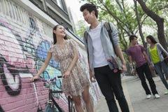 步行沿着向下街道的两对年轻夫妇由有街道画的墙壁,微笑和挥动互相 免版税库存图片
