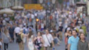 步行沿着向下街道的人大人群  汽车有他们的被转动的车灯 股票录像