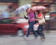步行沿着向下街道的人们在雨天 图库摄影