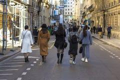 步行沿着向下街道的几个女孩在巴黎,背面图 免版税库存照片