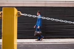 步行沿着向下街道的可爱的商人 免版税库存照片