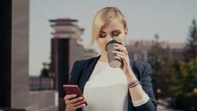 步行沿着向下街道的女实业家白种人出现,带领在的电话和啜饮的一次重要交谈 股票视频