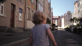 步行沿着向下街道的小的卷曲白肤金发的女孩旅行 股票录像