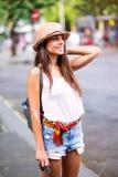 步行沿着向下街道的年轻愉快的旅游妇女 库存照片