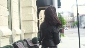 步行沿着向下街道的快乐的女孩 诱惑转过来,笑在照相机 股票录像