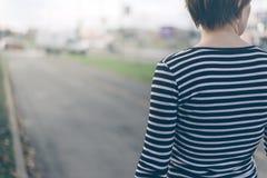 步行沿着向下街道的普通的妇女 免版税图库摄影