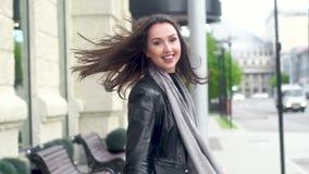 步行沿着向下街道的美女 诱惑转过来,笑在照相机 股票视频