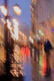 步行沿着向下街道的被弄脏的青年人抽象背景在多雨晚上, ipressionizm样式,五颜六色的光 免版税库存照片