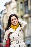 步行沿着向下街道的满意的愉快的妇女 免版税库存照片
