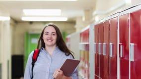 步行沿着向下走廊和微笑对照相机的女性高中学生画象  影视素材