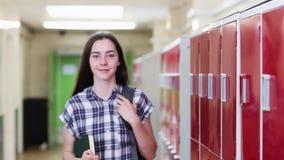 步行沿着向下走廊和微笑对照相机的女性高中学生画象  股票视频