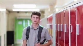 步行沿着向下走廊和微笑对照相机的男性高中学生画象  影视素材