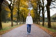 步行沿着向下路的男孩在黄色树之间 库存图片