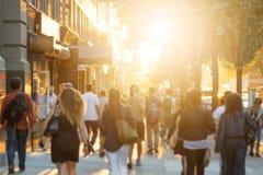 步行沿着向下都市边路的匿名男人和妇女人群  库存图片