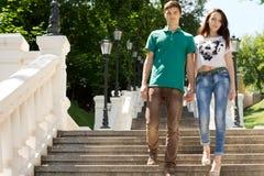 步行沿着向下陡峭的阶梯步级的夫妇 库存照片