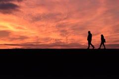 步行沿着向下非常橙色日落的夫妇 免版税库存图片