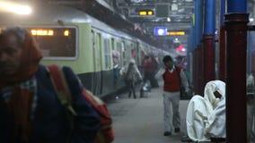 步行沿着向下驻地的人画象,当火车在背景时到达 股票录像