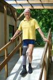 步行沿着向下锻炼的舷梯的资深腿被截肢者 图库摄影