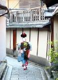 步行沿着向下Gion邻里街道的maiko在京都 免版税库存图片