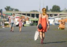 步行沿着向下Naplavka,布拉格的一名美丽的妇女 库存图片