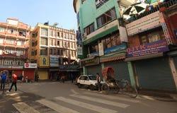 步行沿着向下Thamel街道的尼泊尔人民在日出下早晨在加德满都 免版税图库摄影
