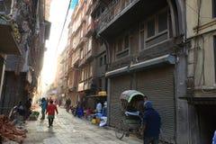 步行沿着向下Thamel街道的尼泊尔人民在日出下早晨在加德满都 图库摄影