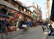 步行沿着向下Thamel街道的尼泊尔人民在日出下早晨 免版税库存照片
