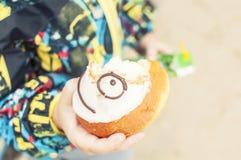 步行的一个男孩吃一个蛋糕,一张兴高采烈的面孔, 免版税库存图片