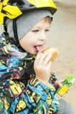 步行的一个男孩吃一个蛋糕,一张兴高采烈的面孔, 库存照片