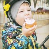 步行的一个男孩吃一个蛋糕,一张兴高采烈的面孔, 免版税图库摄影