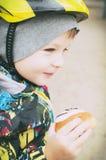 步行的一个男孩吃一个蛋糕,一张兴高采烈的面孔, 图库摄影