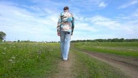 步行的一个英俊的人在单独领域附近 股票录像