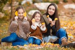 步行的三个姐妹在秋天公园 免版税库存照片