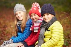 步行的三个孩子通过冬天森林地 免版税图库摄影