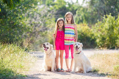 步行的两个姐妹与狗在公园 库存照片