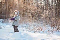 步行的儿童女孩在拿着雪的冬天森林里 库存照片