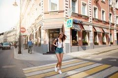 步行的女孩游人在城市夏时附近 免版税库存照片
