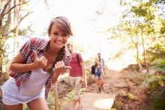 步行的妇女与做滑稽的姿态的朋友在照相机 免版税库存照片